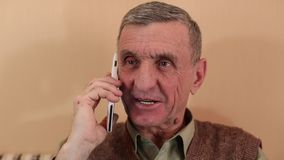 El hombre mayor con el smartphone blanco habla y sonríe almacen de video