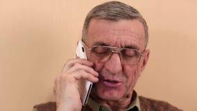 El hombre mayor con el smartphone blanco habla y sonríe metrajes