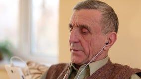 El hombre mayor con el smartphone blanco se sienta en el sofá y escucha la música metrajes