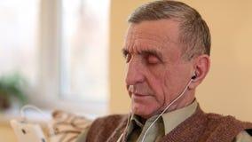 El hombre mayor con el smartphone blanco se sienta en el sofá y escuchar la música metrajes