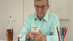 El hombre mayor con el teléfono móvil y la botella blancos de coñac se sienta en una tabla metrajes