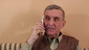 El hombre mayor con smartphone habla la sonrisa y gesticular almacen de metraje de vídeo