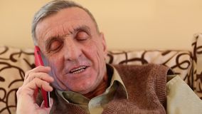 El hombre mayor con smartphone rojo habla y sonríe almacen de video