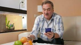 El hombre mayor con un bigote hace una compra de la tarjeta de crédito de la tienda en línea Él se sentaba en casa en el sofá y metrajes