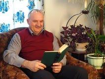 El hombre mayor con un libro en una silla Imagenes de archivo