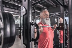 El hombre mayor confiado está haciendo deporte en gimnasio moderno Imágenes de archivo libres de regalías