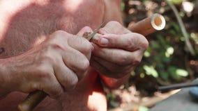 El hombre mayor corta el corcho para hacer una flauta de la obra, primer almacen de video