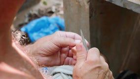 El hombre mayor corta el corcho para hacer una flauta de la obra, primer metrajes