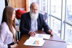 El hombre mayor del jefe firma el documento con el ayudante joven con los papeles Foto de archivo