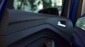 El hombre mayor demuestra el interior de la puerta posterior del nuevo coche almacen de metraje de vídeo