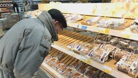 El hombre mayor elige el pan en el supermercado de Lenta metrajes