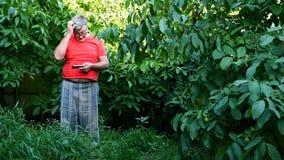 El hombre mayor en ropa casual, quizás un pensionista, utiliza su smartphone en el patio trasero o en el jardín almacen de metraje de vídeo