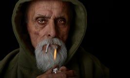 El hombre mayor enciende una junta Imagen de archivo libre de regalías