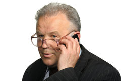 El hombre mayor habla por un teléfono móvil Fotografía de archivo
