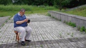 El hombre mayor hace irritable cuando realícelo olvidado para instalar el carrete de película a una cámara media vieja de la pelí almacen de metraje de vídeo