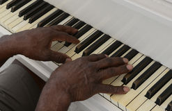 El hombre mayor juega el piano Imagenes de archivo