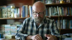 El hombre mayor manosea un libro con los dedos almacen de metraje de vídeo