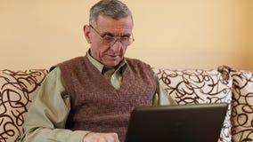 El hombre mayor mecanografía el texto usando el ordenador portátil almacen de metraje de vídeo