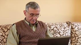 El hombre mayor mecanografía el texto usando el ordenador portátil metrajes