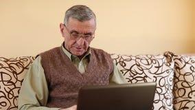 El hombre mayor mecanografía el texto usando el ordenador portátil almacen de video