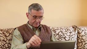 El hombre mayor mecanografía el texto usando el ordenador portátil Hombre en el diván con el cuaderno almacen de video