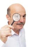 El hombre mayor mira algo a través de una lupa Fotos de archivo libres de regalías