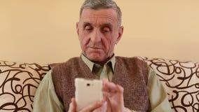 El hombre mayor mira y mueve de un tirón a través de las fotos en su smartphone almacen de metraje de vídeo