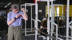 El hombre mayor muestra para poseer el bíceps del brazo en fondo del gimnasio almacen de metraje de vídeo