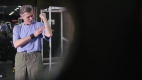 El hombre mayor muestra para poseer el bíceps del brazo en fondo del gimnasio metrajes
