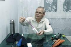 El hombre mayor prepara las cañas de pescar para pescar Fotografía de archivo