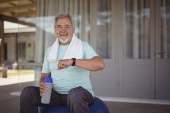 El hombre mayor que comprueba tiempo en el reloj después de se resuelve Foto de archivo libre de regalías