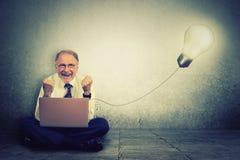 El hombre mayor que trabajaba en el ordenador con la bombilla la enchufó Imagen de archivo libre de regalías