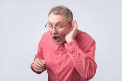 El hombre mayor quiere oír rumores frescas fotografía de archivo libre de regalías