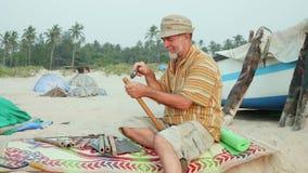 El hombre mayor se sienta en la playa y flauta de la fabricación por las manos almacen de metraje de vídeo