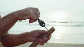 El hombre mayor se sienta en la playa y flauta por las manos, primer de la fabricación metrajes