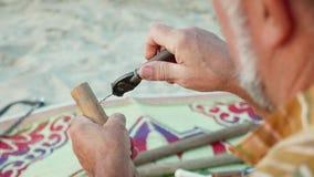 El hombre mayor se sienta en la playa y flauta por las manos, primer de la fabricación almacen de metraje de vídeo