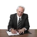 El hombre mayor se sienta en la tabla y escribe el documento fotografía de archivo libre de regalías