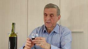 El hombre mayor se sienta en una tabla y bebe el vino almacen de video