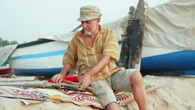 El hombre mayor se sienta y seleccionando los cortes de bambú para hacer la flauta de la obra metrajes