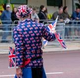 El hombre mayor se vistió en la chaqueta y el sombrero adornados con las banderas del Union Jack, y el Union Jack que agita señal fotos de archivo libres de regalías