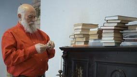 El hombre mayor toma el libro del piano del vintage y lo leyó almacen de video