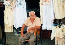 El hombre mayor vende la ropa interior y la ropa en mercado callejero del pueblo turco viejo Fotos de archivo