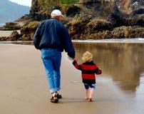 El hombre mayor y el pequeño niño dan un paseo la playa que lleva a cabo las manos imagen de archivo