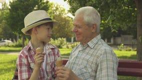 El hombre mayor y su nieto comen el helado en el banco imagenes de archivo