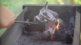 El hombre mezcla los carbones en un brasero el hombre revuelve los carbones el hombre mezcla los carbones en un brasero una pala  almacen de metraje de vídeo