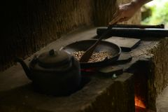 El hombre mezcla los granos de café crudos en un sartén fotografía de archivo