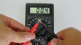 El hombre mide el multímetro digital metrajes