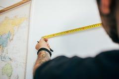 El hombre mide la pared con la cinta métrica imagenes de archivo