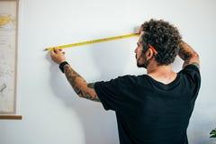 El hombre mide la pared con la cinta métrica imagen de archivo