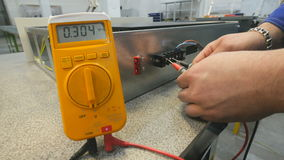 El hombre mide voltaje usando multímetro digital metrajes
